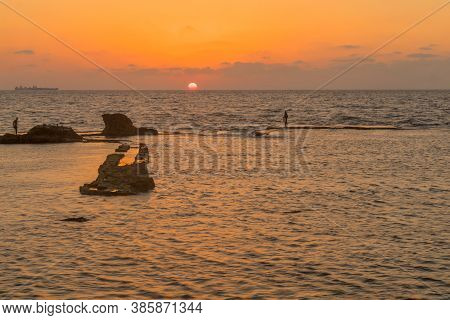 Acre, Israel - September 14, 2020: Sunset View Of The Remains Of A Templar Fortress, With Fishermen,