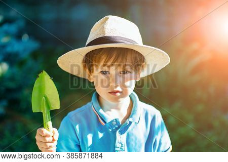 Portrait Of Preschooler Cute Boy With Resolute Expression On Face, Wearing In Straw Hat, Blue T-shir