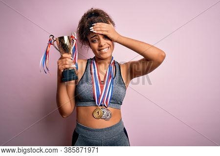 Young african american sporty girl doing sport winning medals and trophy over pink background stressed with hand on head, shocked with shame and surprise face, angry and frustrated. Fear and upset.
