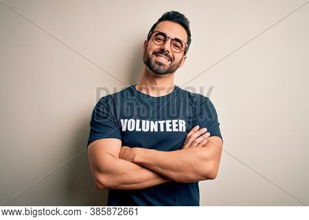 Handsome man with beard wearing t-shirt with volunteer message over white background happy face smiling with crossed arms looking at the camera. Positive person.