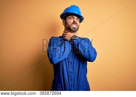 Mechanic man with beard wearing blue uniform and safety helmet over yellow background shouting suffocate because painful strangle. Health problem. Asphyxiate and suicide concept.