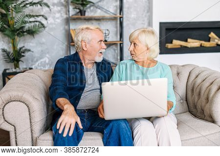 Elderly Spouses Are Sitting At Home On The Couch With A Laptop And Stared At Each Other In Disbelief