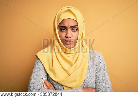 Young beautiful african american girl wearing muslim hijab over isolated yellow background skeptic and nervous, disapproving expression on face with crossed arms. Negative person.