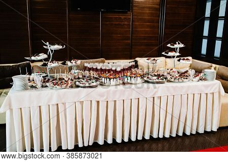 Table With Sweets, Candy, Buffet. Dessert Table For A Party Goodies For The Wedding. Cakes, Cupcakes