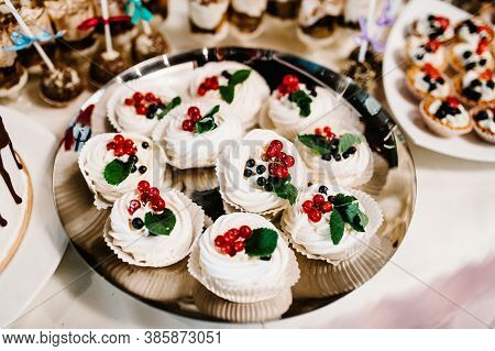 Sweet Table. A Plate Muffins With Cream With Berries. Table With Sweets, Candy, Buffet. Dessert Tabl