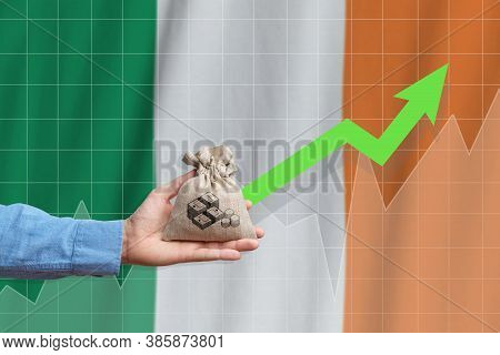 The Concept Of Economic Growth In Ireland. Hand Holds A Bag With Money And An Upward Arrow.