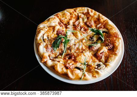 Italian Meat Pizza With Arugula On A Brown Wooden Desk Background. Top Photo. From Top. Delicious Ho