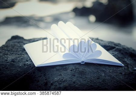 Open Book With White Blank Paper Page Flower Shape Decoration On A Sea Rock. New Life, New Chapter C