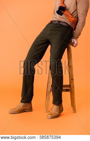 Cropped View Of Trendy Man In Autumn Outfit Sitting On Wooden Stool On Orange