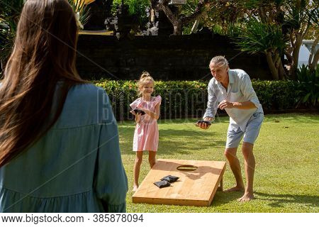 Happy Family Playing Cornhole Game Outdoor On Sunny Summer Day. Parents And Children Playing Bean Ba
