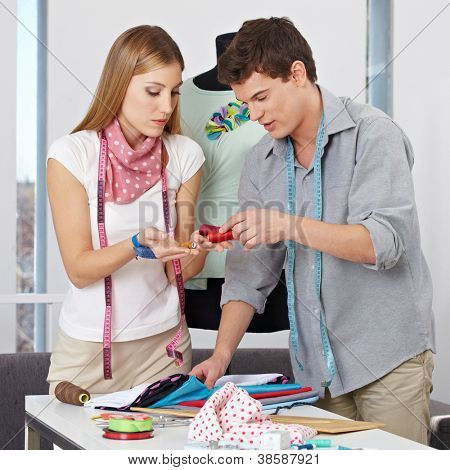 Two fashion designer choosing yarn in studio for their clothing collection