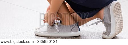 Partial View Of Schoolgirl Tying Laces On Sneaker, Panoramic Shot