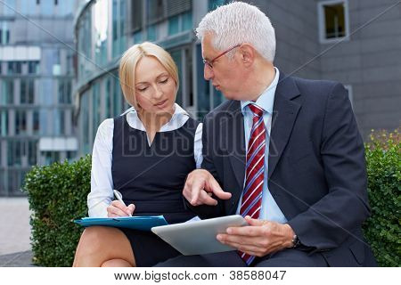 Two business people working with tablet computer outside the office