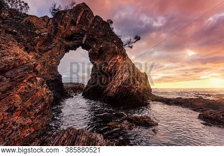 Sunrise Sky At The Towering Pyramidal Rock Arch Formation On The Jagged Coast Line, Striped Veins Te