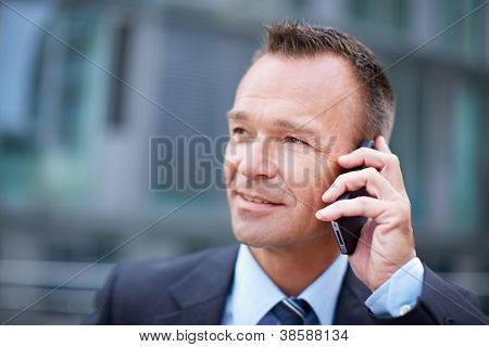 Business man in the city making a phone call with smartphone