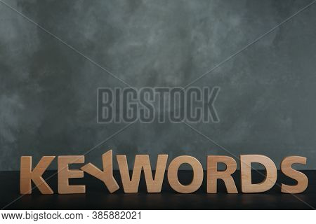 Word Keywords Made Of Wooden Letters On Dark Table. Space For Text