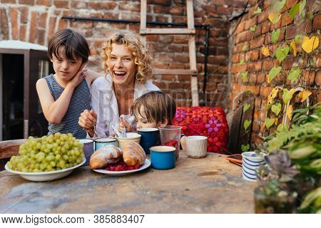 Mother With Two Children Son On Terrace, One Of Them With Down Syndrome At Summer Together. Parentin