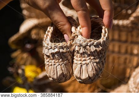 The Girl Holds In Her Hands Souvenir Children's Shoes Made Of Straw, Handmade For Festivals Of Folk