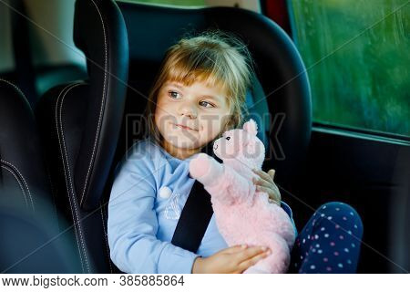 Adorable Toddler Girl Sitting In Car Seat, Holding Plush Soft Toy And Looking Out Of The Window On N