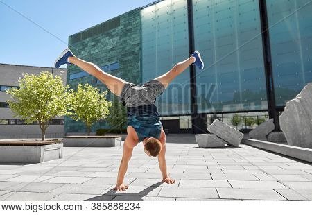 fitness, sport, training and lifestyle concept - young man exercising and doing handstand outdoors