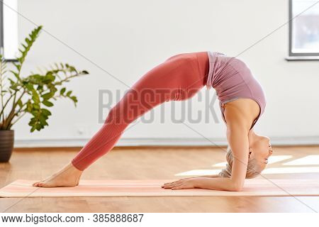 fitness, people and healthy lifestyle concept - young woman doing yoga in upward facing two-foot staff pose at studio
