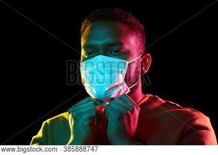 health, safety and pandemic concept - young african american man wearing protective medical mask over black background