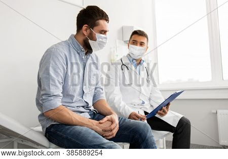 medicine, healthcare and pandemic concept - male doctor wearing face protective medical mask for protection from virus disease with clipboard and young man patient meeting at hospital