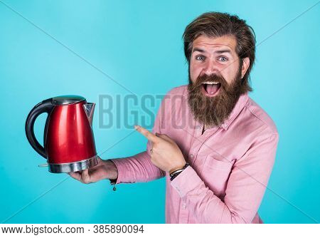 Look Over There. Good Quality. Mature Hipster With Beard Drinking Tea. Brutal Guy With Electric Kett