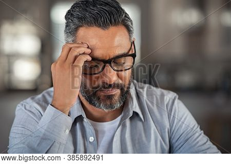 Frustrated middle aged man sitting on couch at home. Close up face of stressed indian businessman wearing eyeglasses with eyes closed. Overworked middle eastern business man with terrible migraine.