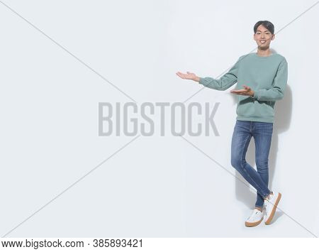 full length handsome casual man wearing green sweater with blue jeans ,white white sneaker handshake as greeting and welcoming