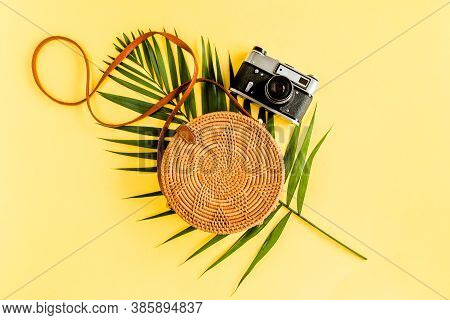 Traveler Accessories Concept On Yellow Background. Fashionable Handmade Natural Round Rattan Bag, Re