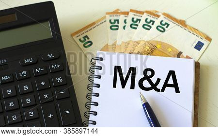 M&a (mergers And Acquisitions) Word In A Notebook Against The Background Of Calculitar And Banknotes
