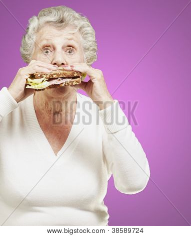 senior woman eating a healthy sandwich against a pink background