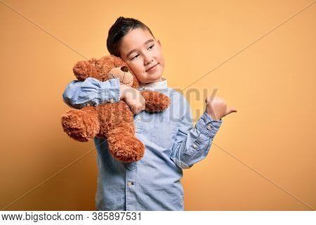 Young little boy kid hugging teddy bear stuffed animal over yellow background pointing and showing with thumb up to the side with happy face smiling