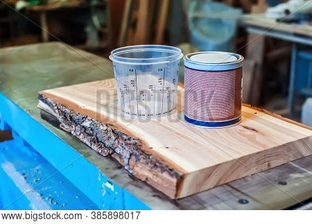 Epoxy Resin And Measuring Container In A Carpentry Shop. Making Furniture With Epoxy Resin