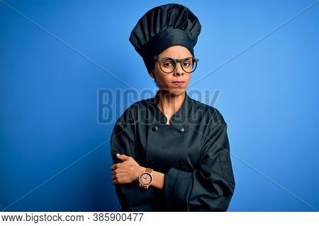 Young african american chef woman wearing cooker uniform and hat over blue background skeptic and nervous, disapproving expression on face with crossed arms. Negative person.