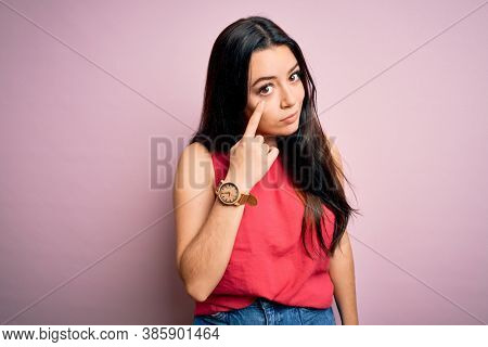 Young brunette woman wearing casual summer shirt over pink isolated background Pointing to the eye watching you gesture, suspicious expression