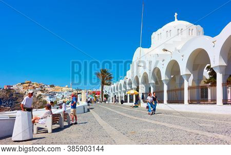 Fira, Santorini island, Greece - April 25, 2018: Promenade with walking people near Metropolitan Cathedral in Fira (Thera)