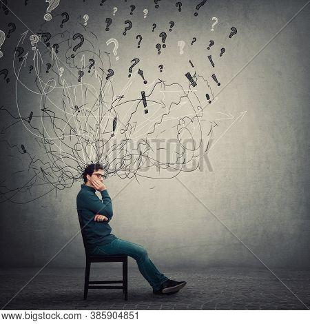 Pessimistic, Disappointed Businessman Sit On Chair, Keeps Hand Under Cheek, Looking Thoughtful And A
