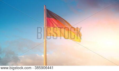 German flag waving on flagpole on blue sky background