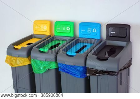 Green, Yellow, Red, Blue Color Plastic Garbage Recycle Bin In Public Place. Background Of Trash Pape