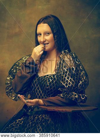 Sunflower Seeds. Young Woman As Mona Lisa, La Gioconda Isolated On Dark Green Background. Retro Styl