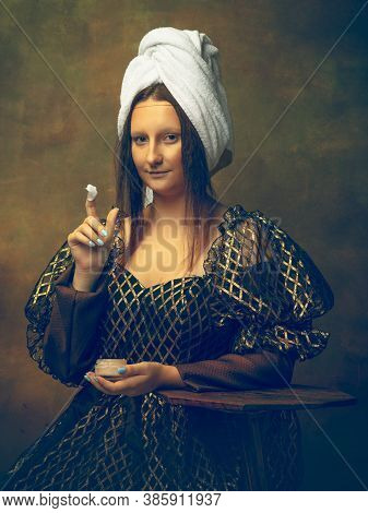 Beauty Routine. Young Woman As Mona Lisa, La Gioconda Isolated On Dark Green Background. Retro Style