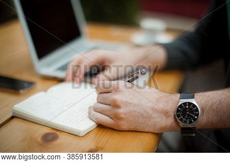 A Business Man Writes With A Pen In A Black Notebook While Sitting At A Table. Smart Watch On A Hand