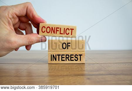 Male Hand Placing A Block With Word 'conflict' On Top Of A Blocks Tower With Words 'conflict Of Inte