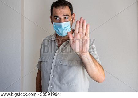 Portrait Of Worried Bearded Man Wearing A Mask To Protest Himself From Coronavirus Dressed In Beige