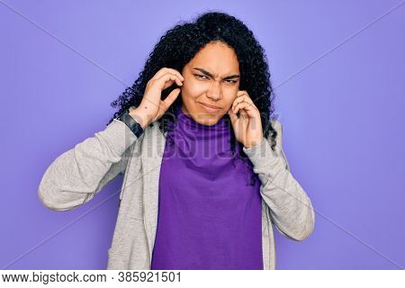 Young african american sporty woman wearing casual sweatshirt over purple background covering ears with fingers with annoyed expression for the noise of loud music. Deaf concept.