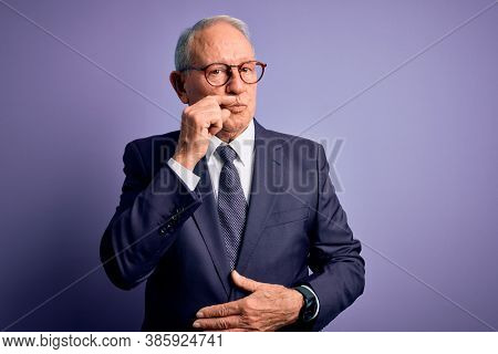 Grey haired senior business man wearing glasses and elegant suit and tie over purple background mouth and lips shut as zip with fingers. Secret and silent, taboo talking