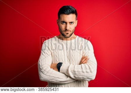 Young handsome man wearing casual white sweater standing over isolated red background skeptic and nervous, disapproving expression on face with crossed arms. Negative person.