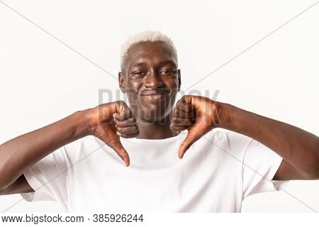 Close-up Of Unamused And Skeptical Black Guy With Blond Hair, Showing Thumbs-down And Smirk With Dis